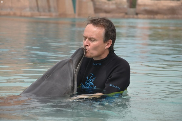 Christopher John Payne kisses dolphin at Atlantis Hotel in Dubai
